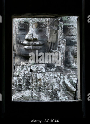 Carved Buddha face seen through temple window. The Bayon, Angkor Thom, Cambodia - Stock Photo