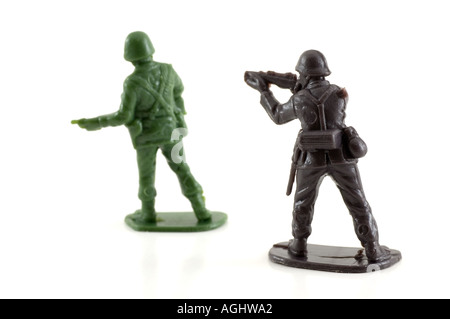 Plastic toy soldiers at war The enemy sneaks up on one unsuspecting soldier - Stock Photo