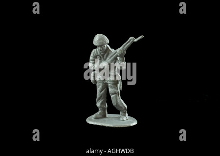 One grey plastic toy soldier against a black background - Stock Photo
