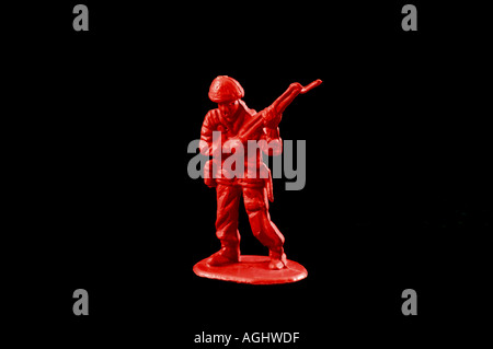 One blood red plastic toy soldier against a black background - Stock Photo