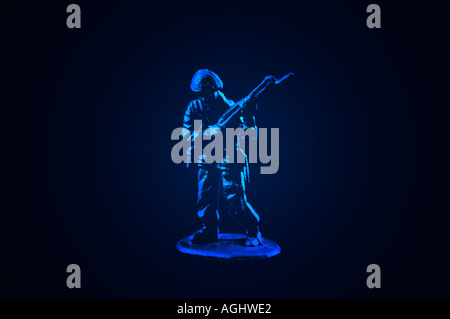 One blue plastic toy soldier against a black background - Stock Photo