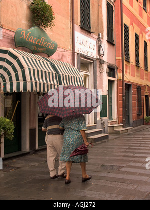 Older couple walking together in the rain under one umbrella Levanto Italy - Stock Photo