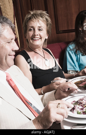 Side profile of a mature woman with a senior man and a mid adult woman having meal - Stock Photo
