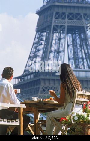 Couple having breakfast on Seine River houseboat across from Eiffel Tower in Paris - Stock Photo