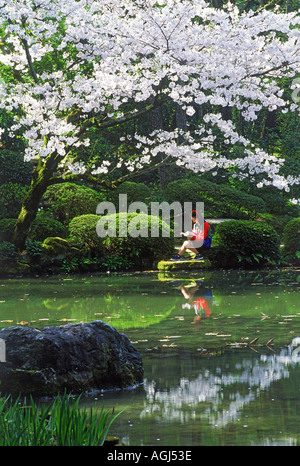Japanese girl seated next to pond reading a book under cherry blossoms in Kyoto park in spring - Stock Photo