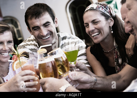 Three mid adult men and two mid adult women toasting their drinks - Stock Photo
