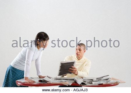 Young professionals looking at newspapers - Stock Photo