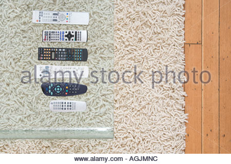 Remote controls on coffee table - Stock Photo