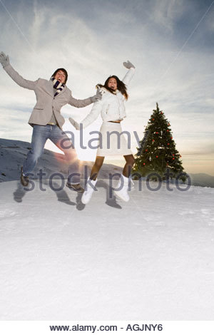 Couple jumping in the snow - Stock Photo