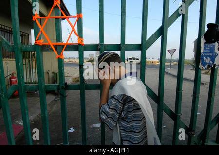 Orange ribbons tied into the gate of Neveh Dekalim symbolizing the struggle against the eviction from Jewish settlements - Stock Photo
