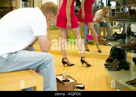 Fed up boyfriend watching woman try on shoes - Stock Photo