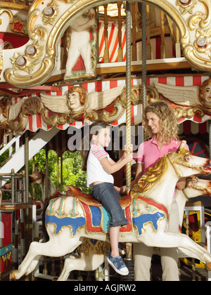 Mother and daughter on carousel - Stock Photo