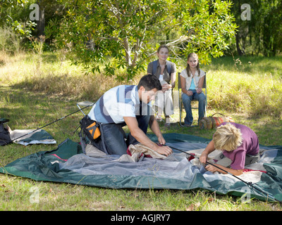 Family putting up tent - Stock Photo
