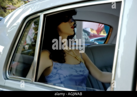 Car with woman inside on back seat mannequin - Stock Photo