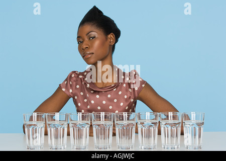 Young woman with eight glasses of water - Stock Photo