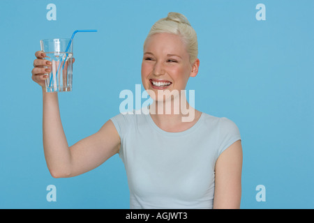 Young woman holding a glass of water - Stock Photo