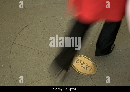 A woman dressed in black pants and a red coat rushes through Faneuil Hall Marketplace past a golden plaque that - Stock Photo