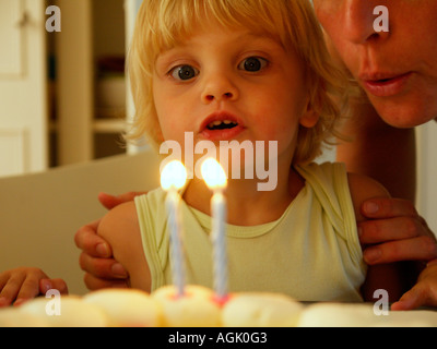 Little girl blowing out two burning candles on her second birthday her name is Irene - Stock Photo