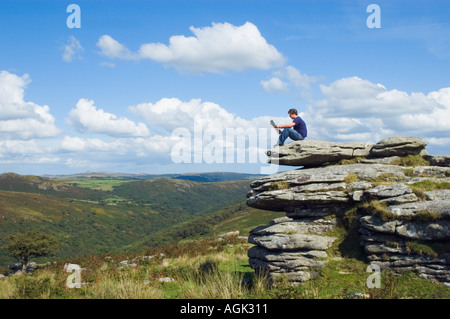 Young man sitting on a rock reading a magazine UK - Stock Photo