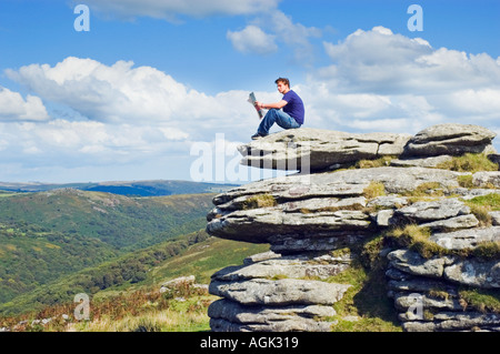 Young man sitting on a rock reading a magazine in open countryside - Stock Photo