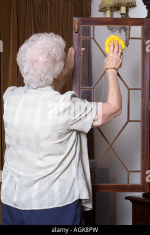 An elderly lady ^dusting - Stock Photo