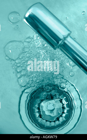 pouring tap with water going down the plug in a sink - Stock Photo