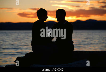 Couple sitting by the water - Stock Photo