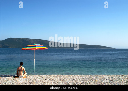 A sunbather sitting under an umbrella at a pebble beach, on the Alonissos Island in Greece. - Stock Photo