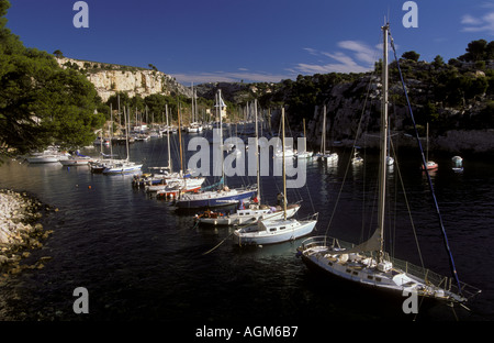 Sailboats anchored in Bay in cliffs of Calanques Provence Mediterranean Sea France - Stock Photo