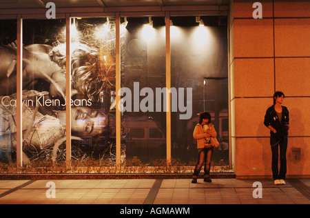 Two Pedestrians Standing Next to Advertisement on People's Square in Shanghai - Stock Photo