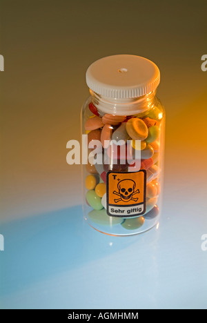 medicin pills in bottle with symbol for poison skull and crossbones - Stock Photo