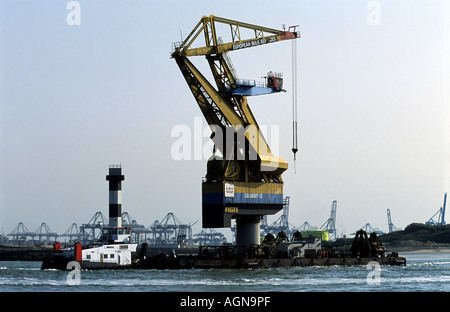 A crane being transported by barge, port of Rotterdam, Holland. - Stock Photo