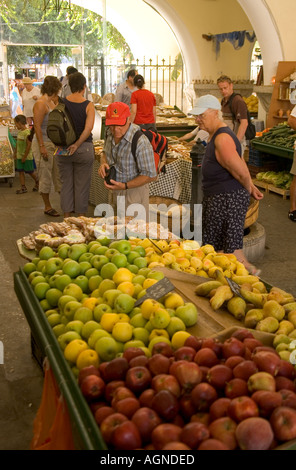 dh  KOS TOWN GREECE KOS Two tourist looking at fruit in local central fruit market - Stock Photo