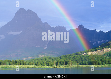 Rainbow over Swiftcurrent lake in Glacier National Park Montana - Stock Photo