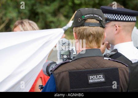 Protestors use a banner to prevent a police photographer from photographing the protestors at the climate camp - Stock Photo