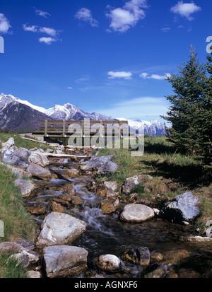 MOUNTAIN STREAM from JOHNSON LAKE with foot bridge Banff Alberta Canada - Stock Photo