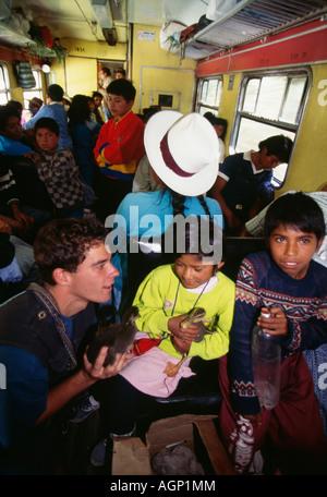 Peru Cusco Tourists and locals in train traveling to Machu Picchu - Stock Photo