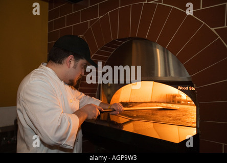 Detroit Michigan Frankie Paulick a line cook at Small Plates restaurant puts a pizza in the oven - Stock Photo