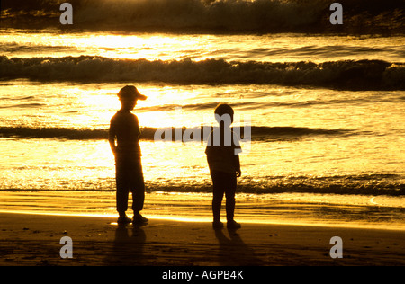 Two teenage boys standing on beach backlit by early morning sunlight - Stock Photo