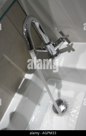 TAP WATER FLOWING DOWN OPEN PLUG HOLE OF WHITE BATHROOM SINK - Stock Photo