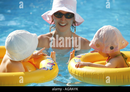 Mother and her babies in swimming pool Summer holiday - Stock Photo