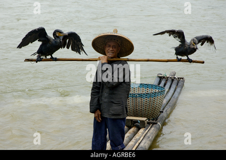 Portrait of a fisherman holding a pole with two cormorants on either side, Li River, Yangshuo, Guangxi, China.