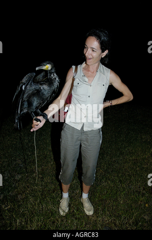 China Guangxi Yangshuo Portrait Of A Woman Holding A Cormorant On Her Arm By Night - Stock Photo