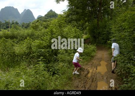 China Guangxi Yangshuo Two Young European Children Walking On A Muddy Dirt Road Along The Rice Paddies - Stock Photo