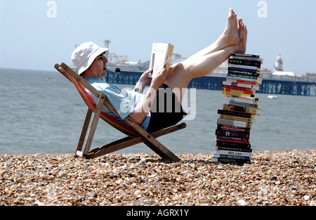 Serious summer reading for a man with a stack of technical books on Brighton beach with the Pier in the background - Stock Photo