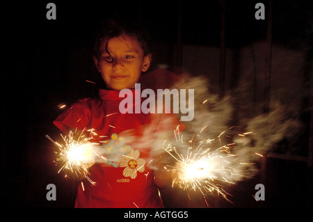 HMA79955 Indian girl holding two burning brightly sparklers fire cracker in her hands on Diwali Festival of lights - Stock Photo