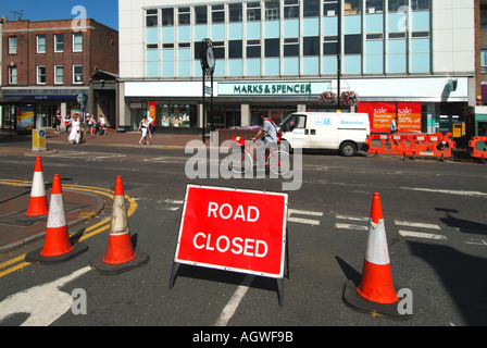Brentwood High Street shopping area traffic closure during water main renewal works postman on bike and contractors - Stock Photo