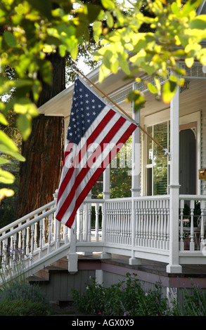 An American flag waves on the front porch of a small town - Stock Photo