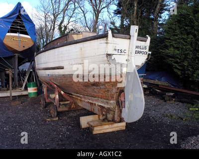 Wooden boat in boatyard for repainting - Stock Photo