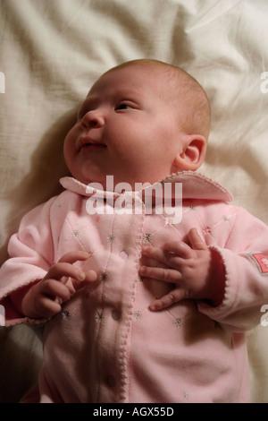 10 week old baby girl in pink sleeper on a cream blanket - Stock Photo